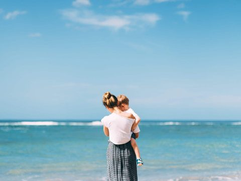 Woman with summer hair holding her child at the beach